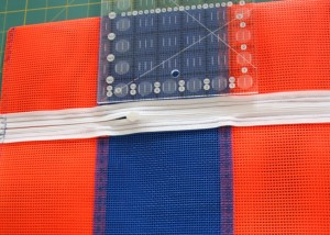 "Find the chalk marks made previously (on each side, 4 1/2"" from the mesh/zipper edge). Make a crease across these marks to form the bag top edge."