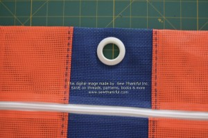 If circle is not quite big enough for grommet to fit, trim carefully with small kids/craft scissors until you have it just right...you want a snug fit.  Then place grommet front and back and SNAP together firmly with your hand using downward pressure on a hard, flat surface.